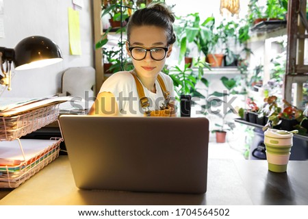 Photo of European female gardener in glasses using laptop, scrolling through social networks, reads news, coffee/tea mug on table, home garden/greenhouse on background. Cozy workplace, remote work