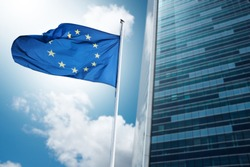 European flag fluttering in the wind in a business district
