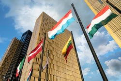 European Flags flapping in the wind, in front of European Union Court of Justice building in Luxembourg Kirchberg. Flags of Luxembourg, Hungary, Lithuania, Austria...