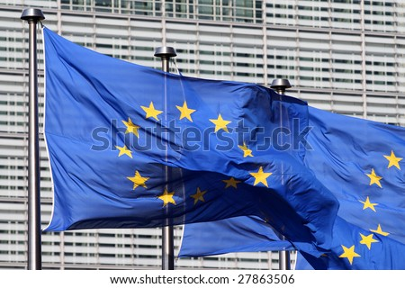 European flags floating in front of the European Commission Building in Brussels, wind blowing from the left