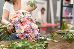 European floral shop concept. Florist woman creates beautiful bouquet of mixed flowers. Handsome fresh bunch. Education, master class and floristry courses. Flowers delivery.
