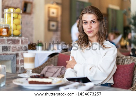 european girl reads e-book in cafe during breakfast. Morning reading. Morning news for breakfast. Coffee and cheesecake on table.
