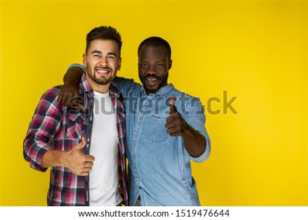european guy and afroamerican guy are laughing and looking in front of them with thumbs up in informal clothes on the yellow background