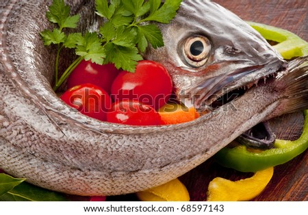 European hake (Merluccius merluccius) being prepared for poaching, in white wine, on a bed of  vegetables and herbs. It is a fierce carnivore as can be seen by its sharp teeth and ferocious eye.