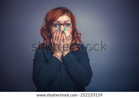 European-looking woman of thirty  years  covers  mouth with  her  hands,  surprised on a gray background retro