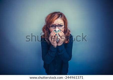 European-looking woman of 30 years is sick, sneezing, handkerchief cross process