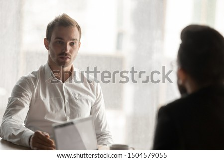 European man applicant answering of questions during job interview in office, business team working together share ideas discuss project details, loan application in bank, hiring partnership concept