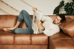 European man in his flat. Sitting in the living room. Bronze skin. Dark eyes and hair. Beard. Light colored interior. Casual clothes style. Weekend at home. Domestic atmosphere. Cosiness and comfort
