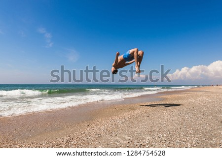European man on the beach of the Black Sea jumps back flip or somersault with a bare-chested in flight against the sky with light clouds #1284754528