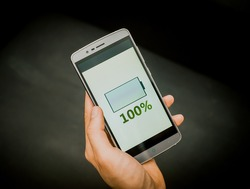 European mans hand holding new silver smartphone on the black background. Full charge is on the screen,