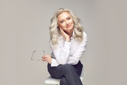 European middle aged female portrait, incredibly gentle senior mature woman dressed in strict business clothing looking at the camera with a adorable and smiling eyes on a grey isolated.
