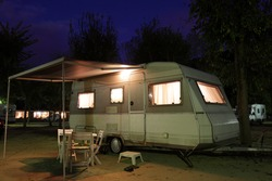 European mobile home on a camping site at night