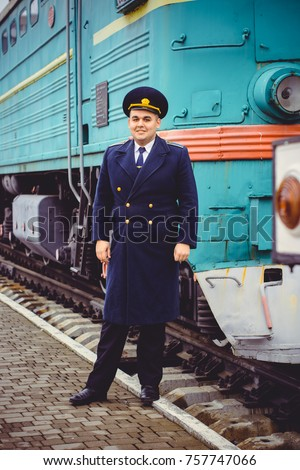 European or American train conductor is on his duty on a platform and other trains. Railway, steam trains, vintage trains #757747066