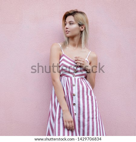 European pretty young blonde woman in a summer stylish striped sundress rests near a pink vintage wall in the city. Beautiful urban girl model outdoors. Fashion women clothes. Summer style.