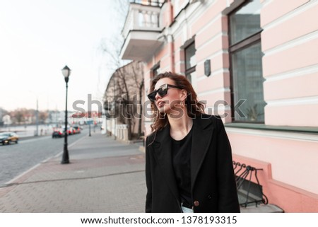 European pretty young hipster woman in trendy sunglasses in a trendy coat in white jeans is standing near a vintage building in the city. Beautiful stylish girl on a walk. Stylish women's clothing. #1378193315