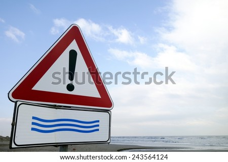 European road traffic sign with a flood warning with blue sky and sea in the background.