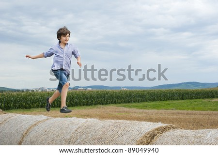 European school-age boy runs through the haystacks in a field in the sky