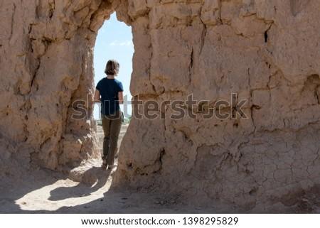 European she-tourist in Kyzyl Kala fortress, one of the most popular touristic destination in the country. Karakalpakstan, Uzbekistan, Central Asia.