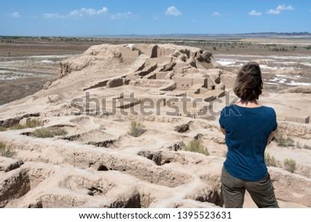 European she-tourist in Toprak-Kala fortress (ancient Capital of Khorezm, one of the most popular touristic attraction in the country). Karakalpakstan, Uzbekistan, Central Asia.
