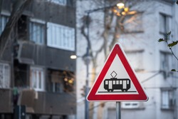 European sign, a tram crossing roadsign, abiding by European traffic regulations, indicating the presence of a a crossroad with a streetcar tram line.