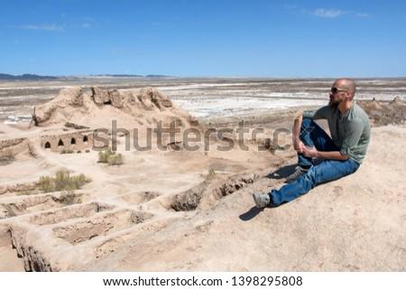 European tourist in Toprak-Kala fortress (ancient Capital of Khorezm, one of the most popular touristic attraction in the country). Karakalpakstan, Uzbekistan, Central Asia.