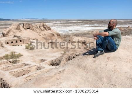 European tourist in Toprak-Kala fortress (ancient Capital of Khorezm, one of the most popular touristic attraction in the country). Karakalpakstan, Uzbekistan, Central Asia. #1398295814