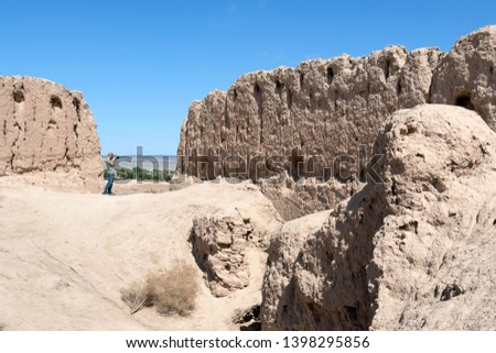 European tourist with photo camera in Kyzyl Kala fortress, one of the most popular touristic destination in the country. Karakalpakstan, Uzbekistan, Central Asia.