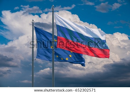 European Union and Russia flags on background of clouds #652302571