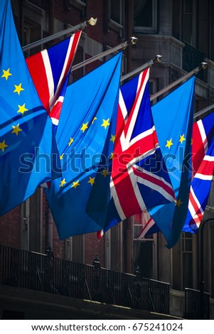 European Union and Union Jack flags in strong sunlight #675241024