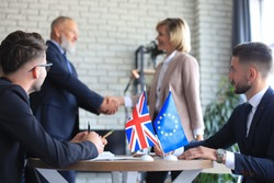 European Union and United Kingdom leaders shaking hands on a deal agreement. Brexit