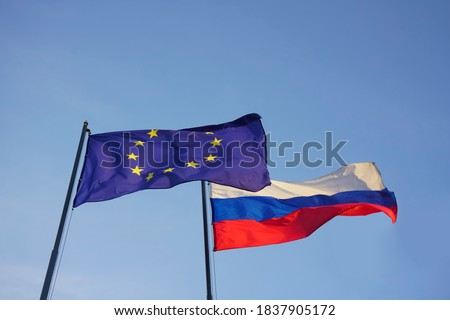 European Union -  EU -  and Russian flags on background of blue sky. empty flag.