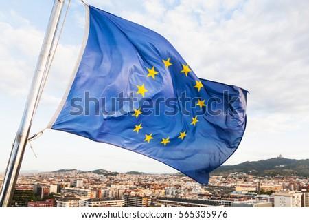 european union flag flutters above Barcelona city #565335976