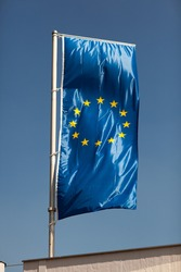 European Union flag flying from a rooftop flagpole against a blue sky