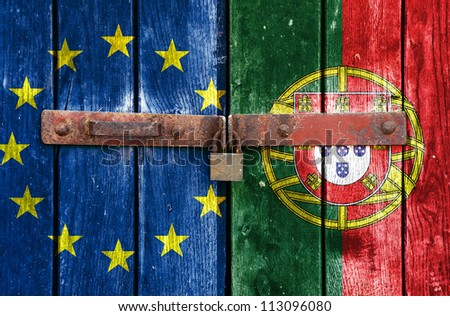 European Union flag with the Portugal flag on the background of old locked doors