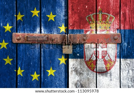 European Union flag with the Serbian flag on the background of old locked doors