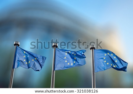 European Union flags in front of the blurred European Parliament in Brussels, Belgium #321038126