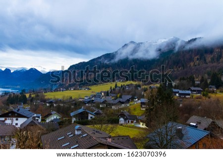 European village moody country side scenic view in morning cloudy autumn weather time rural houses foreground and mountain landscape background