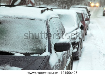 European winter. Snow covered cars.