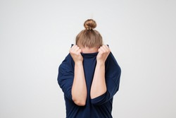 European woman hiding face under the clothes. She is oulling sweater on her head. Depressed emotion. Wish to be alone.