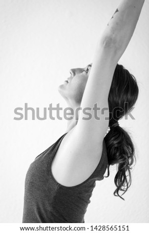 European woman in her mid-thirties practices the dynamic standing yoga pose crescent lunge or Anjaneyasana. Black and white vertical side view.