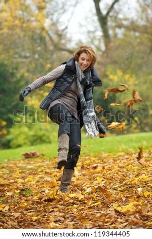 European woman kicking yellow leaves in autumn.