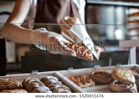 European woman sells in bakery putting bread in paper bag.
