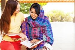 European woman volunteering in Nepal, teaching a poor asian woman to speak English language