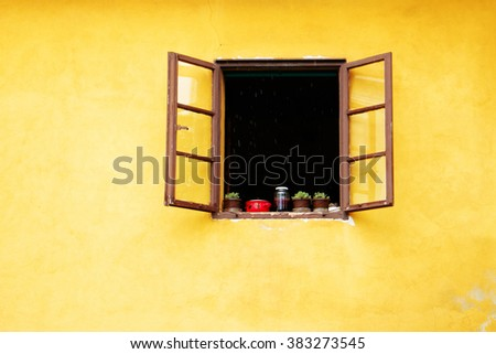 European yellow colorful house wall and window with open wooden shutters, decorated with fresh flowers. Beautiful travel picturesque background, Croatia, Europe.