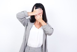 European young business woman wearing checkered suit over isolated white background Covering eyes and mouth with hands, surprised and shocked. Hiding emotions.
