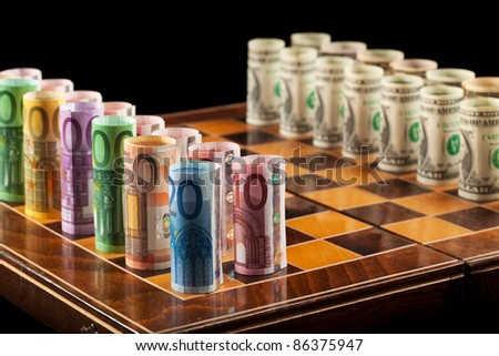 Euros and dollars on chess board - closeup