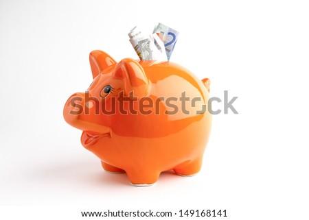 Euros in a orange piggy bank