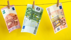 euros on a rope, euro with a clothespin on a rope isolated on a yellow background, Concept - money laundering. euro are dried on the ropes. euros after washing. Money earned honestly. Legalization of