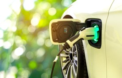 EV Car or Electric car at charging station with the power cable supply plugged in on blurred nature with soft light background. Eco-friendly alternative energy concept