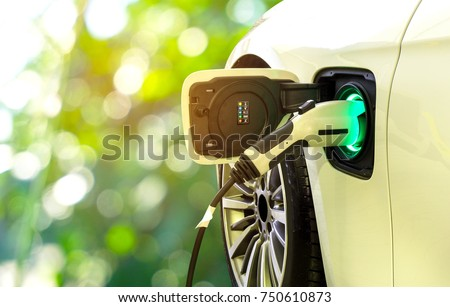EV Car or Electric car at charging station with the power cable supply plugged in on blurred nature with soft light background. Eco-friendly alternative energy concept  Stockfoto ©